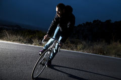 Cyclist man riding fixed gear sport bike. On a mountain road. Nocturne image Stock Photo