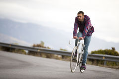 Cyclist man riding fixed gear sport bike in sunny day. On a mountain road Stock Images