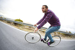 Cyclist man riding fixed gear sport bike in sunny day Stock Images