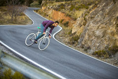 Cyclist man riding fixed gear sport bike in sunny day. On a mountain road Stock Photos