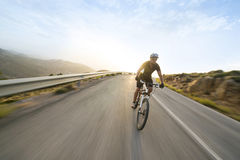Cyclist man riding mountain bike in sunny day royalty free stock photo