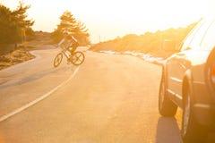 Cyclist man riding mountain bike at sunset Stock Photos