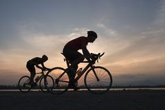 Cyclist in maximum effort in a road outdoors at sunset royalty free stock photo
