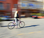Cyclist in motion going down the street Stock Images