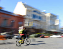 Cyclist in motion going down the street Stock Photo