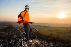Cyclist on mountain-bike  background of beautiful sunset. Royalty Free Stock Images