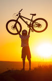 Cyclist with mountain bike on the hill in the evening Stock Photos