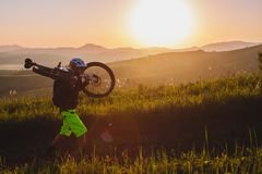 A cyclist on a mountain bike rises uphill. And looks at the scenic landscape. In Altai Stock Image