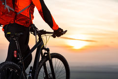 Cyclist on mountain-bike at sunset, cyclist on the background of beautiful sunset. Royalty Free Stock Images