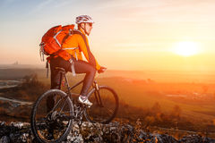 Cyclist with mountain bike on top observing the view. At sunset with lens flare. Beautiful landscape with sunset, hill and rocks. Man with backpack, helmet and royalty free stock photography