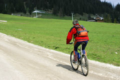 Cyclist on mountain track. Male cyclist on Alpine path Stock Photography