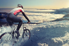 Cyclist. In the mountains, snow road stock photo