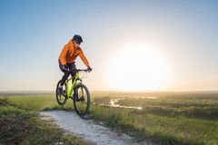 A cyclist in an orange hoodie rides a bike along a mountain path. The concept of extreme sports. Training in the mountains royalty free stock photos