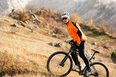 Cyclist in Orange Jacket Riding the Bike Rocky Hill. Extreme Sport Concept. Space for Text. Royalty Free Stock Photo