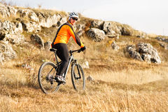 Cyclist in Orange Jacket Riding the Bike Rocky Hill. Extreme Sport Concept. Space for Text. Stock Image