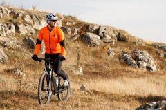 Cyclist in Orange Jacket Riding the Bike on the Rocky Trail. Extreme Sport Concept. Space for Text. Stock Photos