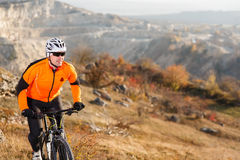 Cyclist in Orange Jacket Riding the Bike on the Rocky Trail. Extreme Sport Concept. Space for Text. Royalty Free Stock Image