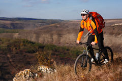Cyclist in the orange jacket standing with his bike on the top of a hill against beautiful landscape. Royalty Free Stock Images