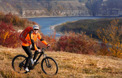 Cyclist in orange jacketr riding bike on the hill under river against beautiful landscape. Royalty Free Stock Photos