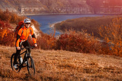 Cyclist in orange jacketr riding bike on the hill under river against beautiful landscape. Stock Photos