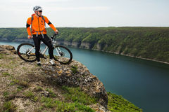 Cyclist in Orange Wear Riding the Bike above River Stock Photos