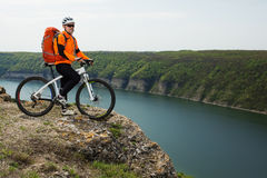 Cyclist in Orange Wear Riding the Bike above River Stock Photography