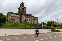 A cyclist passes the Memorial Gardens and Wallasey Town Hall