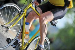 Cyclist pedalling bicycle. Close up of legs of cyclist pedalling bicycle Stock Images
