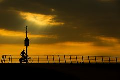 Cyclist on pier at sunset royalty free stock photos