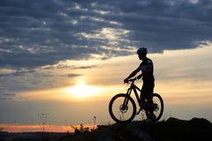 Cyclist posing with bicycle on hill in twilight. stock image