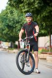 Cyclist posing near bike on city street stock photos