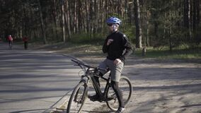 Cyclist puts on pollution mask. Young guy in respirator with pm 2.5 filter before leaving forest in city pollution