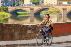 Cyclist on quay of river Arno in Florence, Italy Stock Image