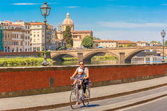 Cyclist on quay of river Arno in Florence, Italy Stock Photos