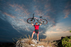 Cyclist raising the mountain bike above his head with success Stock Photography