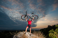 Cyclist raising the mountain bike above his head with success Stock Photo
