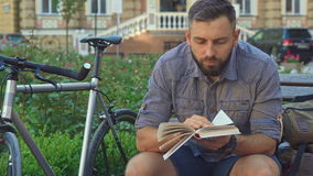 Cyclist reads book on the bench. Attractive bearded cyclist reading book on the bench. Young caucasian man looking at the page of some literature. Handsome stock footage
