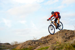 Cyclist in Red Jacket Riding the Bike Down Rocky Hill. Extreme Sport. Royalty Free Stock Image