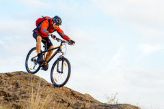 Cyclist in Red Jacket Riding the Bike Down Rocky Hill. Extreme Sport. Stock Photos