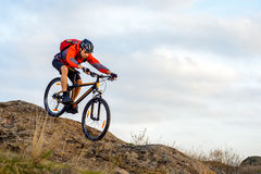 Cyclist in Red Jacket Riding the Bike Down Rocky Hill. Extreme Sport. Royalty Free Stock Photography