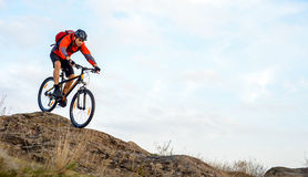 Cyclist in Red Jacket Riding the Bike Down Rocky Hill. Extreme Sport. Royalty Free Stock Photos