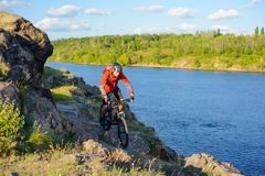 Cyclist in Red Jacket Riding Mountain Bike on the Beautiful Spring Rocky Trail above the River. Extreme Sport Concept Stock Images