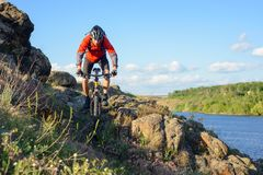 Cyclist in Red Jacket Riding Mountain Bike on the Beautiful Spring Rocky Trail above the River. Extreme Sport Concept Royalty Free Stock Image