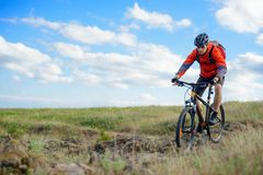 Cyclist in Red Jacket Riding Mountain Bike on the Beautiful Spring Rocky Trail. Extreme Sport Concept Royalty Free Stock Images