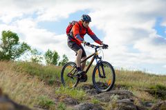 Cyclist in Red Jacket Riding Mountain Bike on the Beautiful Spring Rocky Trail. Extreme Sport Concept Stock Images