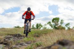 Cyclist in Red Jacket Riding Mountain Bike on the Beautiful Spring Rocky Trail. Extreme Sport Concept Stock Photo