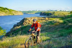 Cyclist in Red Jacket Riding Mountain Bike on the Beautiful Spring Trail above Blue River. Travel and Adventure Sport Concept. Cyclist in Red Jacket Riding the Royalty Free Stock Photos