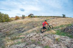 Cyclist in Red Picking the Bike up on Autumn Rocky Trail. Extreme Sport and Enduro Biking Concept. Stock Photography