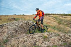Cyclist in Red Riding the Bike on Autumn Rocky Trail. Extreme Sport and Enduro Biking Concept. Royalty Free Stock Image
