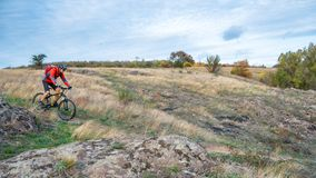 Cyclist in Red Riding the Bike on Autumn Rocky Trail. Extreme Sport and Enduro Biking Concept. Royalty Free Stock Photos